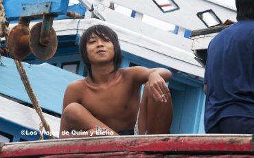 Chico fumando sobre un barco