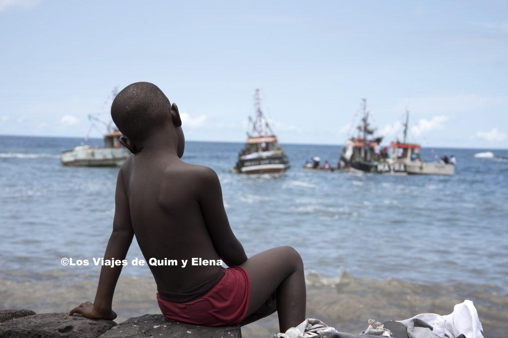Un niño observando los barcos